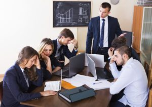 Manager shouting to employees at group meeting indoors