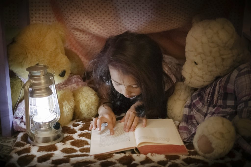 A pretty little girl is reading a book to her teddy bears. They are all hiding inside a fort made of chairs and blankets. An electric lantern is lighting up the interior of the fort, and the pages of the book she's reading.