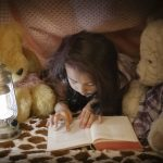 A pretty little girl is reading a book to her teddy bears. They are all h